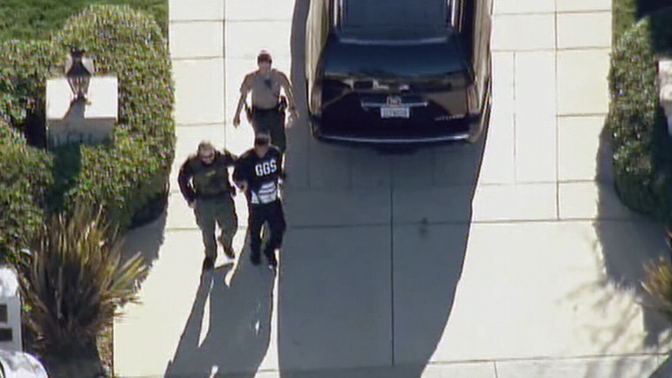 Police escort a person away in handcuffs following a search at Justin Bieber's home in Calabasas, Calif., Tuesday, Jan. 14, 2014.