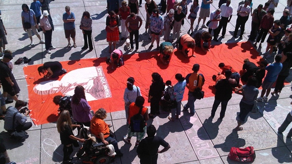 An orange flag in honour of Jack Layton lies in front of Toronto City Hall on Friday, Aug. 26, 2011.