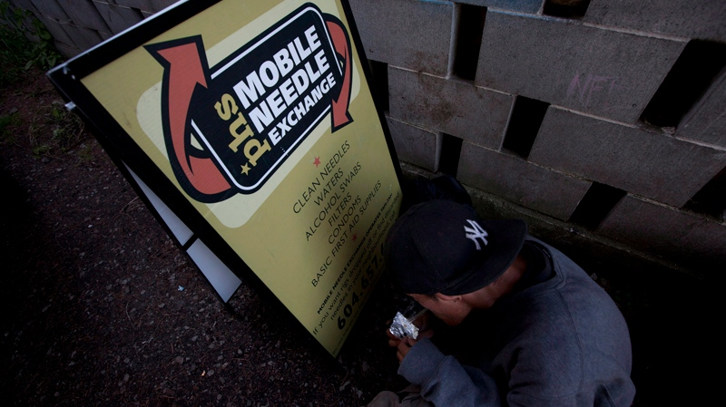 An addict uses the sign for the Portland Hotel Societies mobile needle exchange program to block the wind as he tries to smoke a rock of crack in a alley in Abbotsford, B.C., Thursday, July 5, 2012. (THE CANADIAN PRESS / Jonathan Hayward)