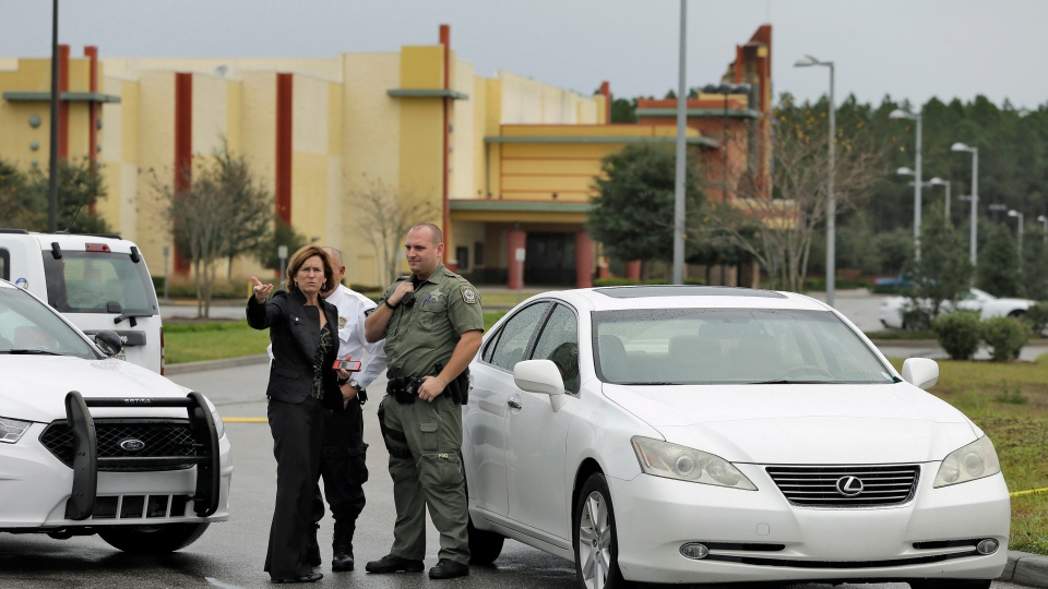 Property manager Helen Ciesla, left, gestures as she talks to a Pasco County sheriff's deputy outside the driveway to the Cobb theater Tuesday, Jan. 14, 2014, in Wesley Chapel , Fla. (AP / Chris O'Meara