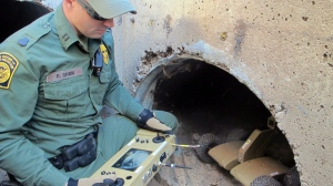 U.S. Border Patrol Agent Ryan Grimm demonstrates how a robot is used to navigate a drainage canal along the border fence during a briefing in Nogales, Ariz., Tuesday, Jan. 14, 2014.  (AP Photo/Brian Skoloff)