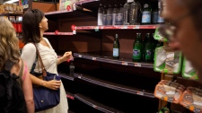 A shopper hunts for water bottles among the empty shelves at a downtown Manhattan supermarket where workers claim over 400 cases were purchased in a few hours, Friday, Aug. 26, 2011.(AP / John Minchillo)