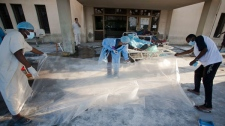 Libyan medical volunteers roll out the plastic sheets in the Abu Salim hospital in Tripoli, Libya, Friday, Aug. 26, 2011. (AP / Giulio Petrocco)