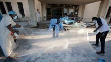 Libyan medical volunteers roll out the plastic sheets in the Abu Salim hospital in Tripoli, Libya, Friday, Aug. 26, 2011. (AP / Giulio Petrocco)