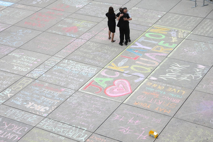 People hug on chalk messages for late NDP Leader Jack Layton outside Toronto City Hall early Friday, Aug. 26, 2011. Layton will lie in repose at city hall pending his state funeral in Toronto on Saturday. (Ryan Remiorz / THE CANADIAN PRESS)