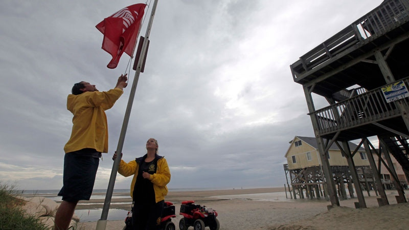 Nags Head Ocean Rescue lifeguards Ben Mechak, left, an Erika Audfroid hoist a no swimming flag in Nags Head, N.C., Friday, Aug. 26, 2011 as Hurricane Irene takes aim at the North Carolina coast. (AP / Gerry Broome)