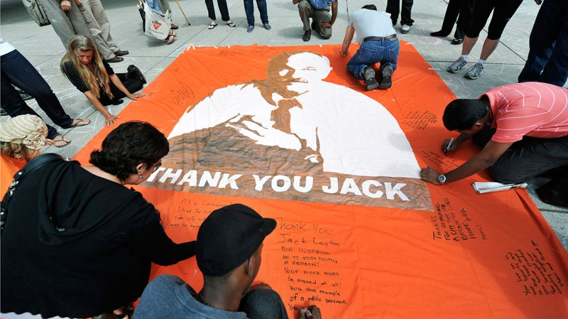 People pay their respects as they write messages on the sidewalks and a banner remembering late NDP leader Jack Layton in Toronto City Hall in Toronto on Friday, August 26, 2011. (Nathan Denette / THE CANADIAN PRESS)