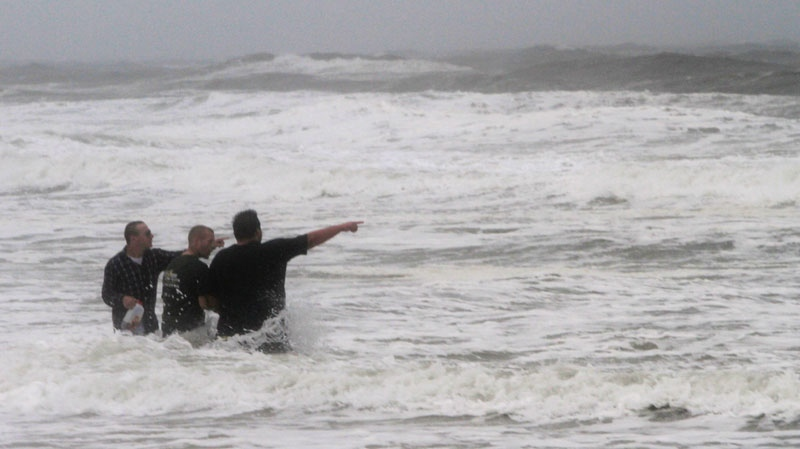 Virginia Beach visitors point out the waves as Hurricane Irene approaches the region in Virginia Beach, Va., Saturday, Aug. 27, 2011. (AP / Steve Helber)