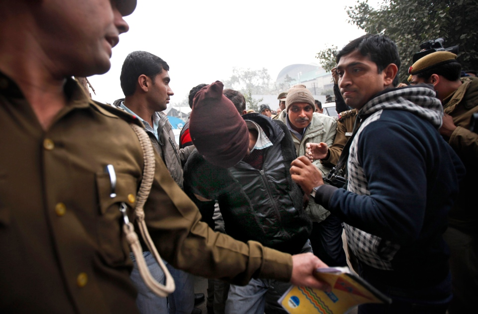 Police officials escort an accused in the gang rape of a 51-year-old Danish tourist to produce him in court in New Delhi, India, Thursday, Jan. 16, 2014. (AP / Altaf Qadri)