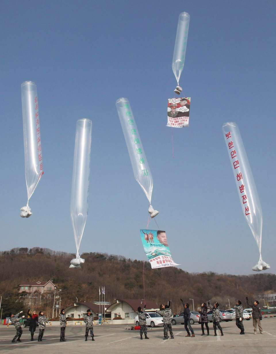 North Korean defectors and human right activists release balloons due to fly to the North, carrying leaflets to condemn North Korean leader Kim Jong Un and U.S. banknotes, during an anti-North Korea rally in Paju, near the demilitarized zone between the two Koreas, South Korea, Wednesday, Jan. 15, 2014. (AP / Ahn Young-joon)