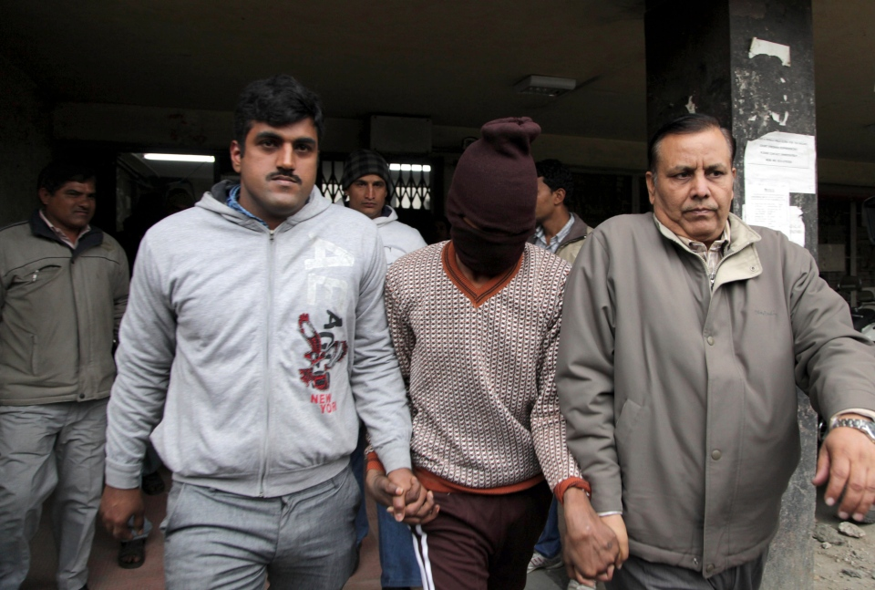Police officials escort an accused in the gang rape of a 51-year-old Danish tourist as they walk out of a court in New Delhi, India, Thursday, Jan. 16, 2014. (AP / Tsering Topgyal)