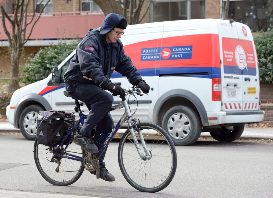 A postal worker rides his bike past a Canada Post van in Toronto on Wednesday, Dec. 11, 2013. (Frank Gunn / THE CANADIAN PRESS)