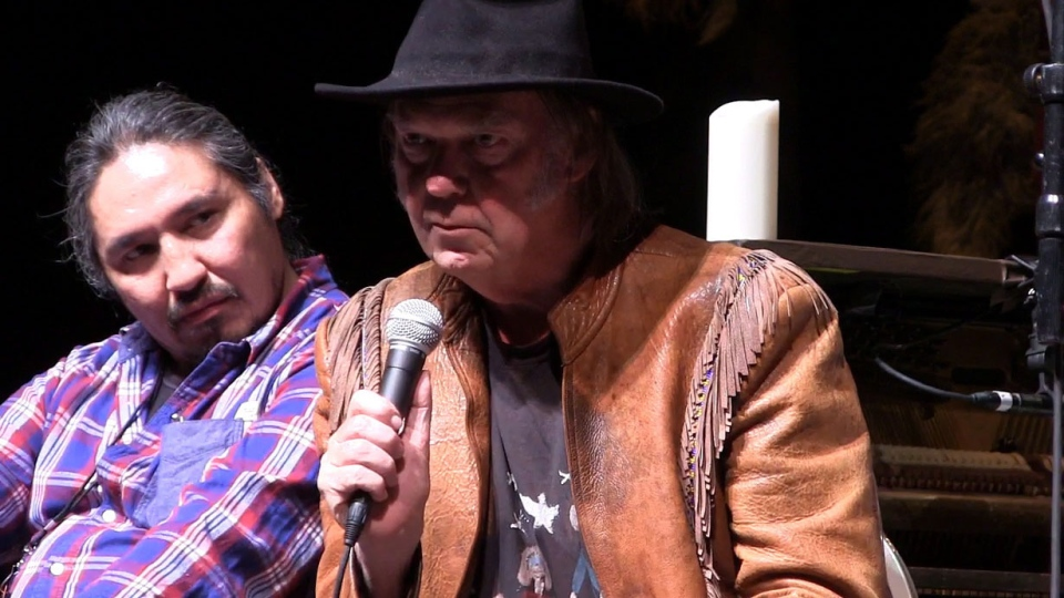 Singer Neil Young is shown speaking in this video frame grab at a Winnipeg news conference on Thursday, Jan. 16, 2014. Athabasca Chipewyan Chief Allan Adam sits to the left of Young. (Steve Lambert / THE CANADIAN PRESS)