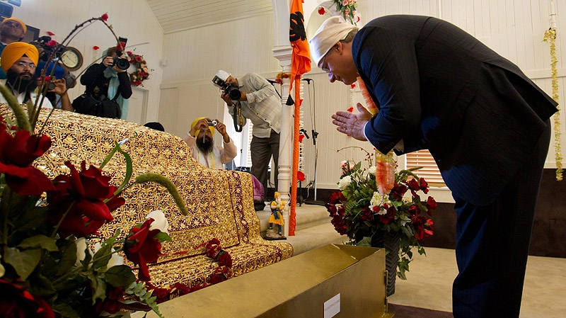 Prime Minister Stephen Harper bows after making a donation while attending an event celebrating the 100th anniversary of the Gur Sikh Temple in Abbotsford, B.C., on Sunday August 28, 2011. The temple is the oldest in North America and is a National Historic Site of Canada. (THE CANADIAN PRESS/Darryl Dyck)