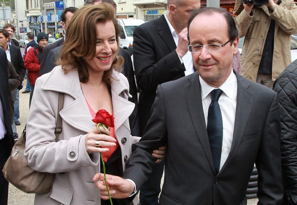 In this May 5, 2012 file photo, French Socialist Party candidate for the presidential election Francois Hollande, right, offers a rose to his companion Valerie Trierweiler, in Tulle, southwestern France. (AP / Bob Edme)