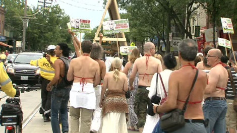 Traffic came to a halt Saturday afternoon as protestors marched the street topless after city officials denied them a special event permit to rally at a public park.
