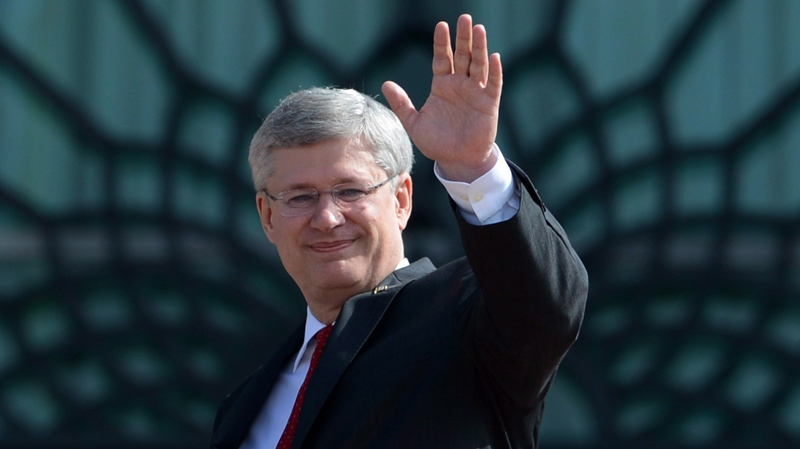 Prime Minister Stephen Harper waves as he meets with Prime Minister of Malaysia Mohd Najib in Putrajaya on Sunday, October 6, 2013. (THE CANADIAN PRESS/Sean Kilpatrick)