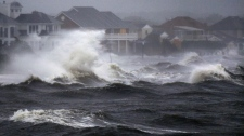 Waves crash over the shore during high tide during a storm surge from Hurricane Irene in Bayshore, N.Y., on Long Island, Sunday, Aug. 28, 2011. (AP / Charles Krupa)
