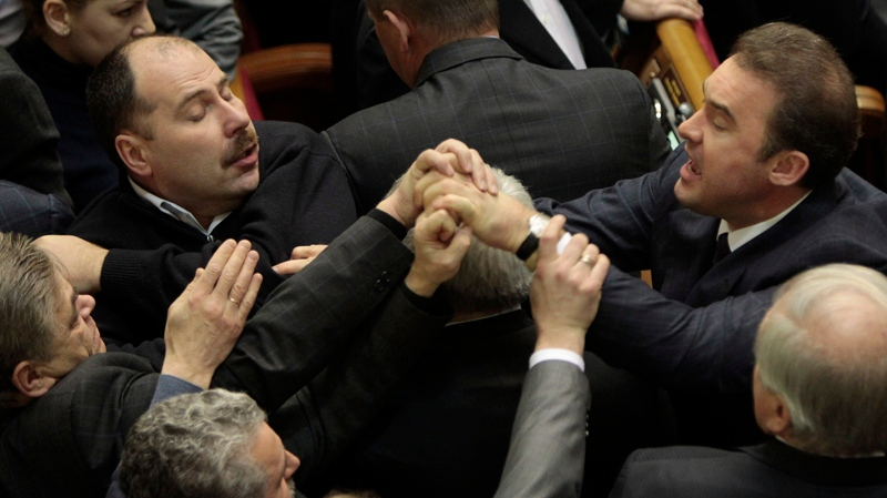 Ukrainian lawmakers scuffle in the Ukrainian parliament in Kiev, Ukraine, Thursday, Jan. 16, 2014. Lawmakers scuffled in the Ukrainian parliament during a debate on this year's budget. Despite the opposition's efforts to disrupt the vote, the budget draft, which has already been delayed by almost two months, was passed in its second reading. (AP / Sergei Chuzavkov)