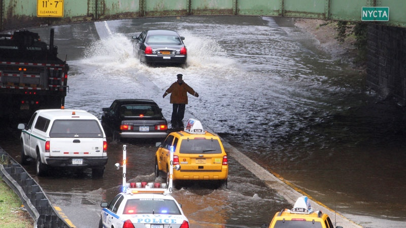 A police officer slows down traffic due to flooding on a section of the Grand Central Parkway caused by heavy rain from Tropical Storm Irene in Queens, New York, on Sunday, Aug. 28, 2011. (AP / Gregory Payan)