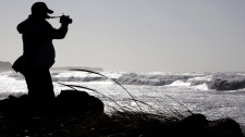 An unidentified man takes photos of the waves at Lawrencetown Beach near Halifax on Monday, Aug. 29, 2011.  (Andrew Vaughan / THE CANADIAN PRESS)