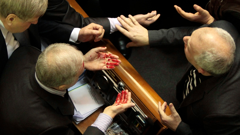Ukrainian pro-government lawmaker Volodymyr Malyshev, left, wipes blood from his face after a scuffle in the Ukrainian parliament in Kiev, Ukraine, Thursday, Jan. 16, 2014. (AP / Sergei Chuzavkov)