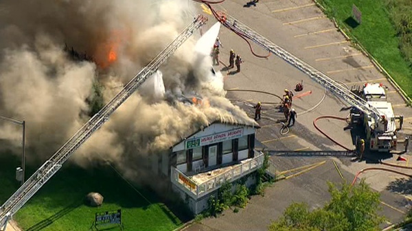 Flames can be seen on the roof of the Double Dragon Delights restaurant in Bowmanville on Monday, Aug. 29, 2011.
