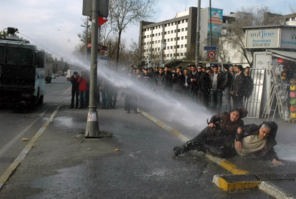 A woman and man resist pressurized water used by riot police to dislodge them, as they stage a sit-in protest in Istanbul, Turkey, Saturday, Jan. 18, 2014. The two were protesting the detention of seven other leftist protesters. (AP Photo)
