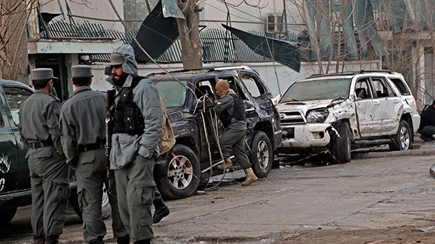 Afghan security forces personnel investigate the site of Friday's suicide attack and shooting, in Kabul, Afghanistan, Saturday, Jan. 18, 2014. (AP / Rahmat Gul)