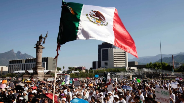 A Mexican flag waves as people demonstrate during a protest in Monterrey, northern Mexico, Sunday, Aug. 28, 2011. (AP / Arnulfo Franco)