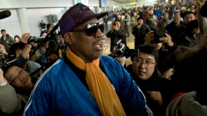 Former NBA basketball player Dennis Rodman is followed by journalists as he arrives at the Capital International Airport in Beijing from Pyongyang, Monday, Jan. 13, 2014. (AP Photo/Alexander F. Yuan)