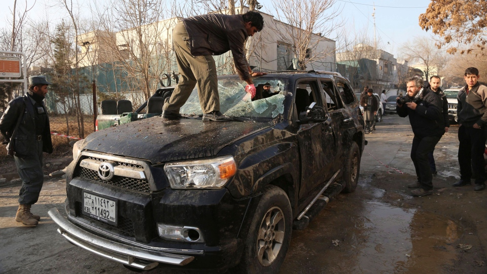 An Afghan driver removes a broken windshield of his car following the Friday's suicide attack and shooting in Kabul, Afghanistan, Saturday, Jan. 18, 2014. (AP / Rahmat Gul)