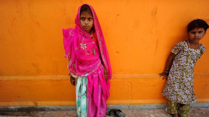 A newly married child bride, left, stands at a temple in Rajgarh, about 155 kilometres from Bhopal, India on Friday, May 6, 2011. (AP Photo/Prakash Hatvalne)