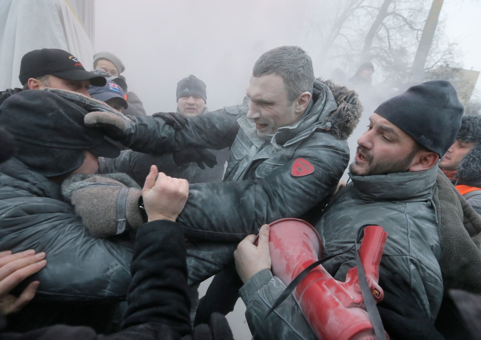 Opposition leader and former WBC heavyweight boxing champion Vitali Klitschko, center, is attacked and sprayed with a fire extinguisher as he tries to stop the clashes between police and protesters in central Kyiv, Ukraine, Sunday, Jan. 19, 2014. (AP /  Efrem Lukatsky)