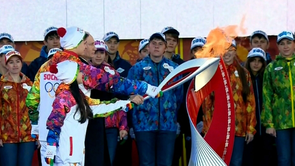 Russian President Vladimir Putin lights the Olympic flame with a torch at Moscow's Red Square.