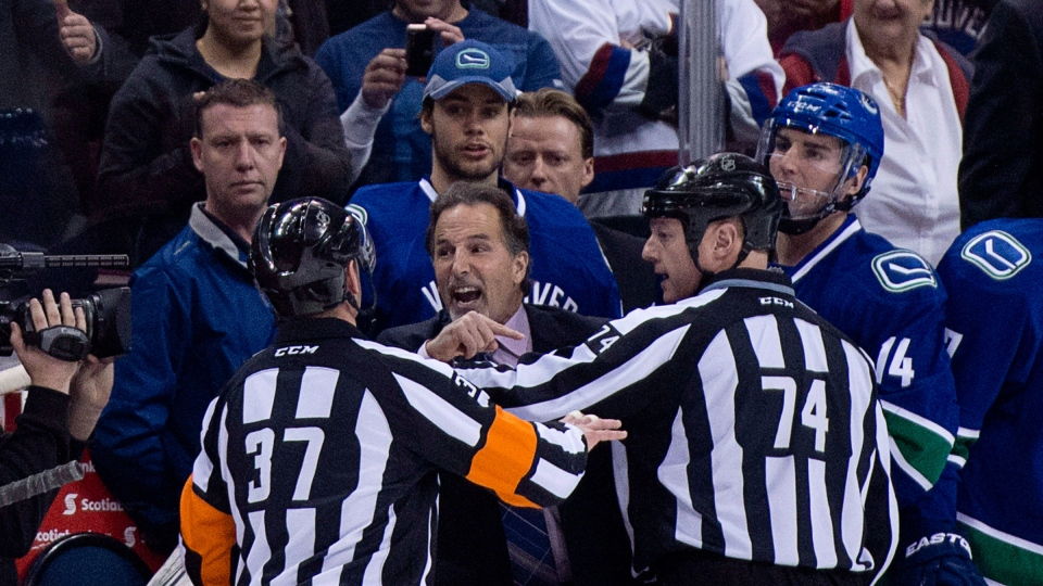 Referees get in the way of Vancouver Canucks head coach John Tortorella as he screams at the Calgary Flames bench during first period NHL hockey action at Rogers Arena in Vancouver, B.C. Saturday, Jan. 18, 2014. (Jonathan Hayward / THE CANADIAN PRESS)