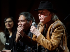 Singer Neil Young, right, makes a point as he speaks during a news conference before the last concert in his 'Honour the Treaties' tour in Calgary, Sunday, Jan. 19, 2014. (Jeff McIntosh / THE CANADIAN PRESS)