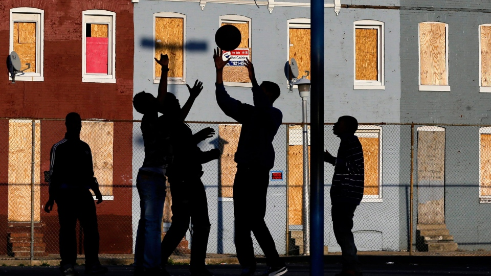 Children play basketball at a park near blighted row houses in Baltimore. Oxfam says in a new report that details the 'pernicious impact,' that widening economic inequality is having worldwide. (AP / Patrick Semansky)