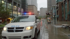 Police block a street in downtown Montreal on Sunday Aug. 28, 2011. Panes of glass from the Rogers building from the 6th and 19th floor fell from the building as Irene reaches the area. THE CANADIAN PRESS/Shaney Komulainen