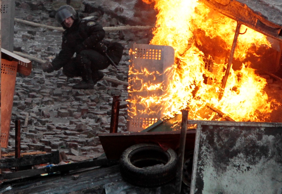 A riot policeman picks up a stone while in front of him a police riot shield burns from a thrown petrol bomb in the main square of Kyiv, Ukraine, Monday, Jan. 20 2014. (AP / Sergei Chuzavkov)