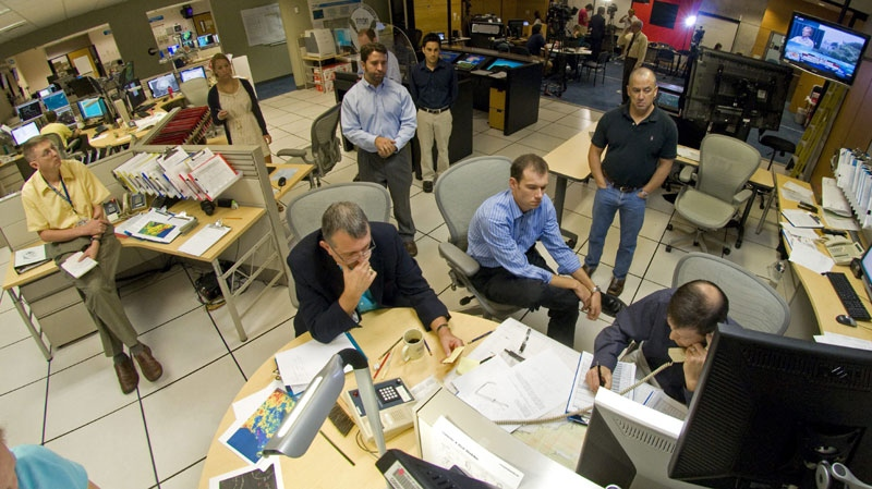 Personnel at the National Hurricane Center in Miami, including NHC director Bill Read, center bottom, conduct a conference call to coordinate the 11 a.m. ET forecast for Hurricane Irene, Saturday, Aug. 27, 2011. (AP Photo/Andy Newman)