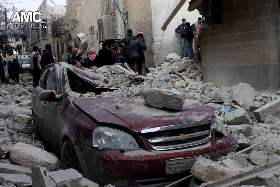 Syrian citizens inspect a destroyed car and a house after a Syrian forces warplanes attack, in Aleppo, Syria on Sunday, Jan. 19, 2014. (Aleppo Media Center / AMC)