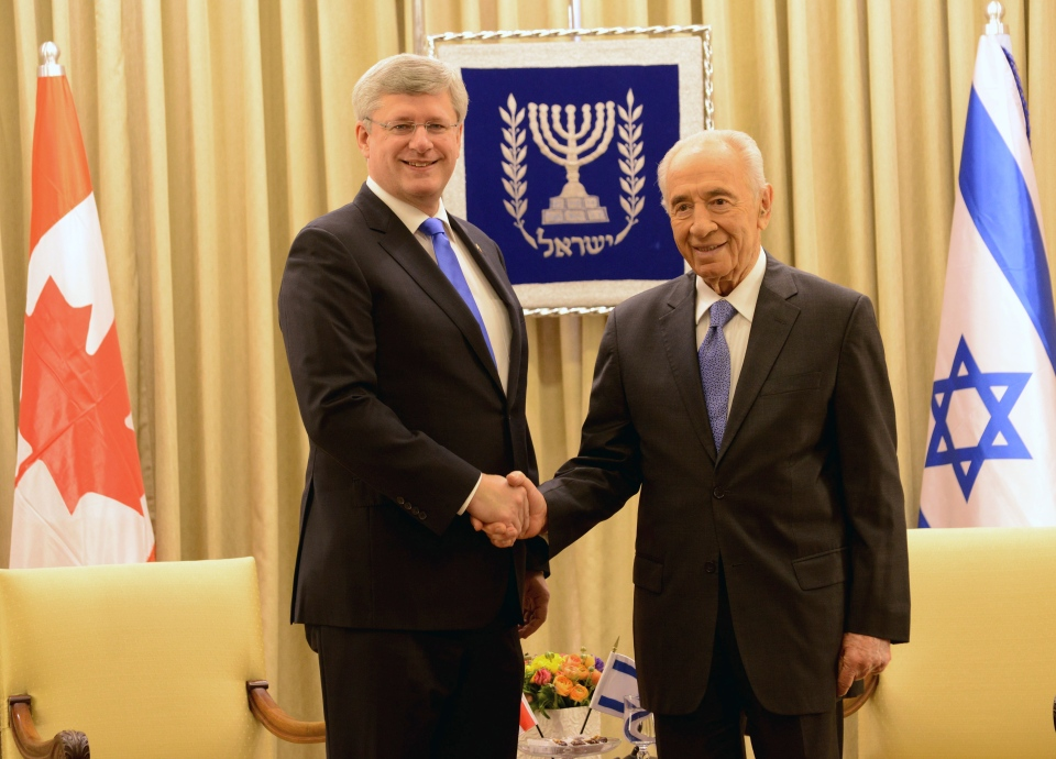 Israeli President Shimon Peres, right, and Canadian Prime Minister Stephen Harper, left, shake hands for photographers before a working meeting in the presidential residence in Jerusalem, Tuesday, Jan. 21, 2014. (AP / Debbie Hill)