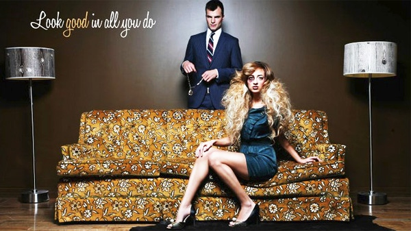 One of the ads in the Fluid Salon campaign features a young woman sitting on a floral couch with a black eye. She has perfectly coiffed hair and is wearing high heels and a stylish dress.