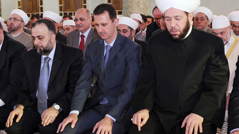 In this photo released by the Syrian official news agency SANA, Syrian President Bashar Assad, center, prays during the Eid al-Fitr prayer at Hafez al-Assad mosque, in Damascus, Syria, on Tuesday Aug. 30, 2011. (AP / SANA)
