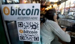 A Bitcoin ATM sticker is posted to the window of a coffee shop in downtown Vancouver, Monday, Oct. 28, 2013. (THE CANADIAN PRESS/Jonathan Hayward)