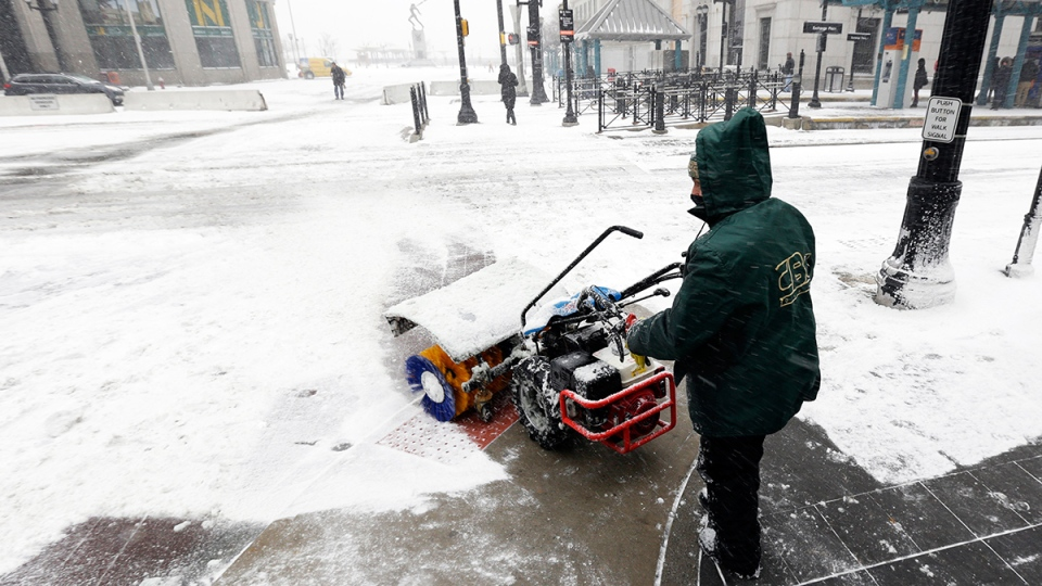 A man plows snow on the sidewalk at Exchange Place as a snow storm moved into the area in Jersey City, N.J., Tuesday, Jan. 21, 2014. (AP / Julio Cortez)