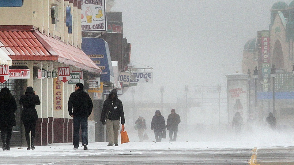 People walk the snow-covered Boardwalk during snowfall, Tuesday, Jan. 21, 2014, in Atlantic City, N.J. (The Press of Atlantic City /  Ben Fogletto)