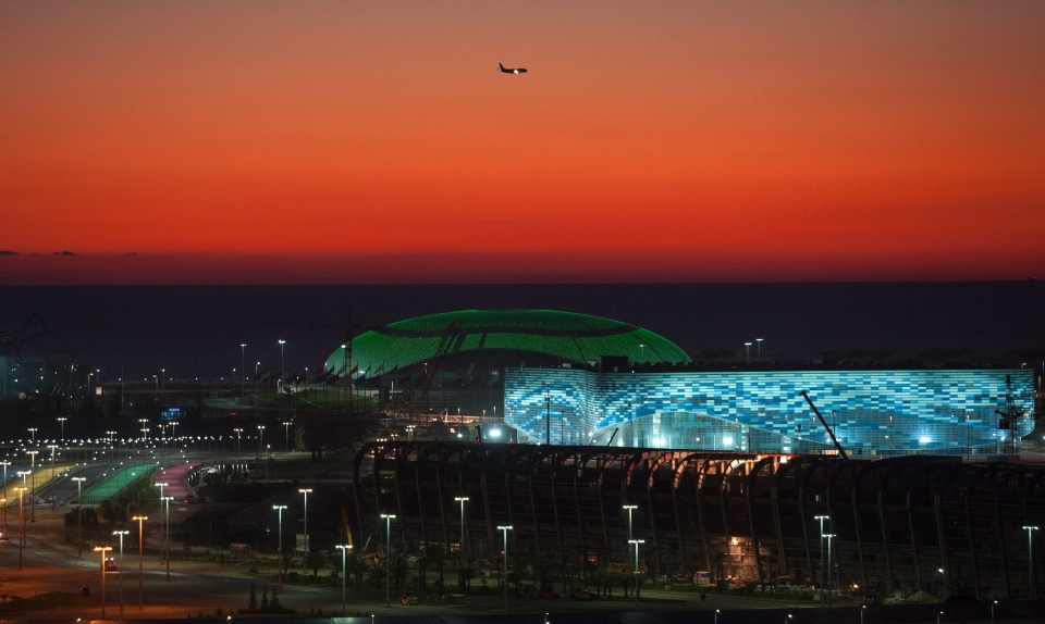 The Olympic Bolshoy stadium, in the background, and Iceberg stadium for figure skating and short track speed skating events during the 2014 Olympic Games, are illuminated in the Olympic park on Thursday, Oct. 24, 2013. (AP / Lesya Polyakova)