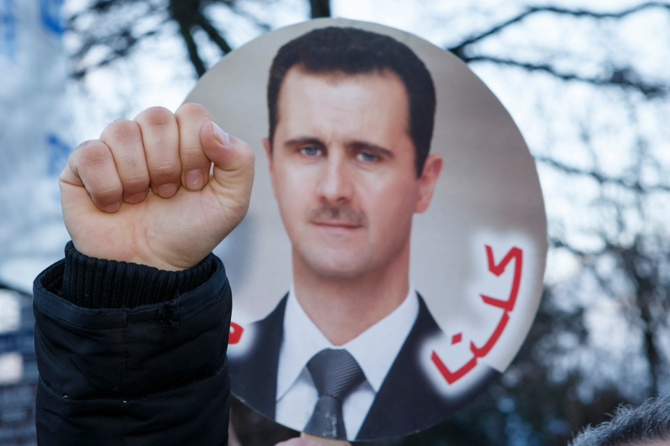 A demonstrator clenches a fist in front of a photo of Syrian President Bashar Assad near the venue of the of the Geneva II peace talks in Montreux, Switzerland, Wednesday, Jan. 22, 2014. (AP / Keystone, Salvatore Di Nolfi)